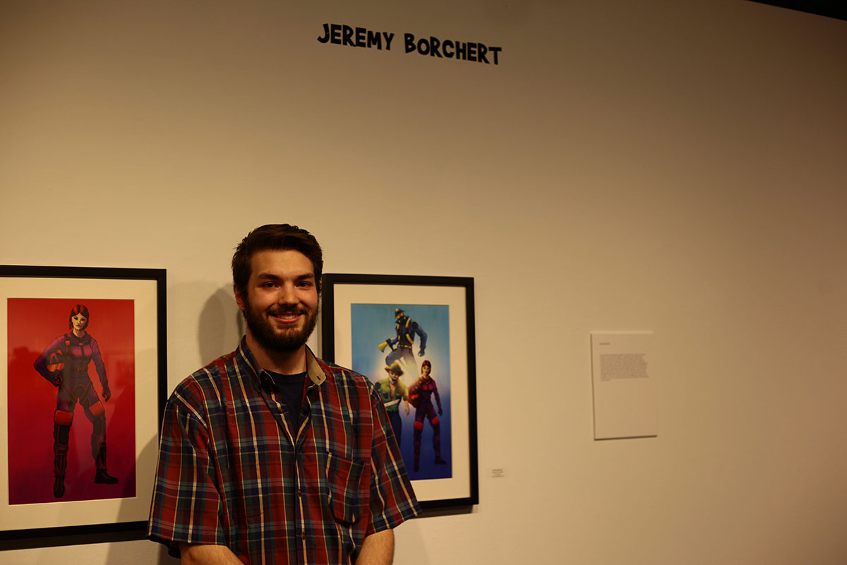 Jeremy+Borchert%2C+an+illustration+student%2C+stands+next+to+his+posters+inspired+by+the+video+game+%E2%80%9CHalo.%E2%80%9D