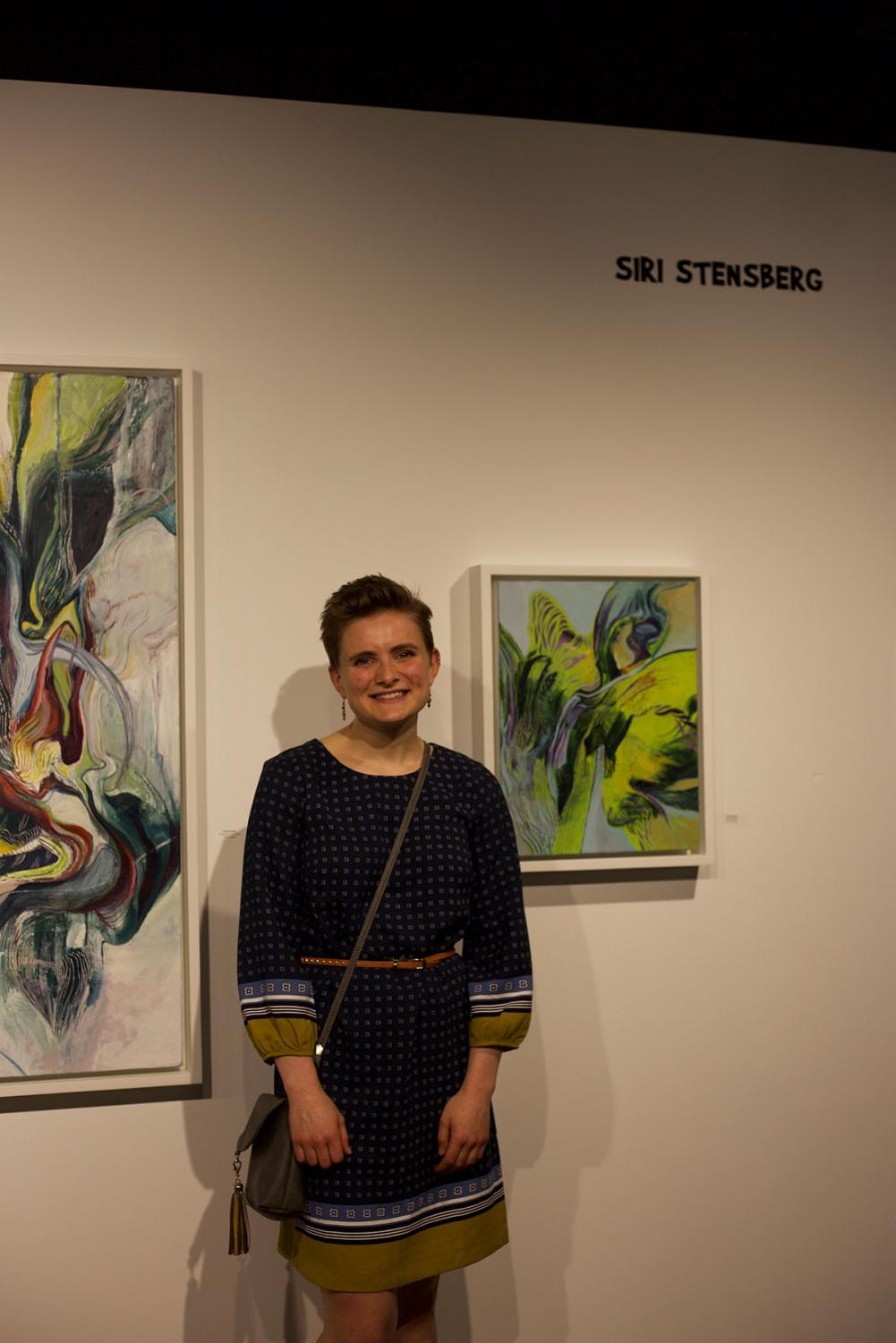 Siri+Stensberg%2C+a+fourth-year+drawing+and+painting+student%2C+stands+next+to+a+few+of+her+presentations.+