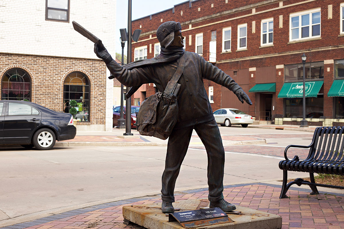 A+bronze+sculpture+represents+the+action+of+a+paperboy+bundled+up+in+the+representation+of+Midwest+cold+seasons.+
