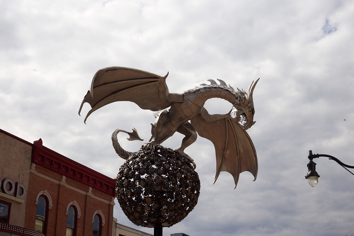 A strong metal dragon gazes over the public.