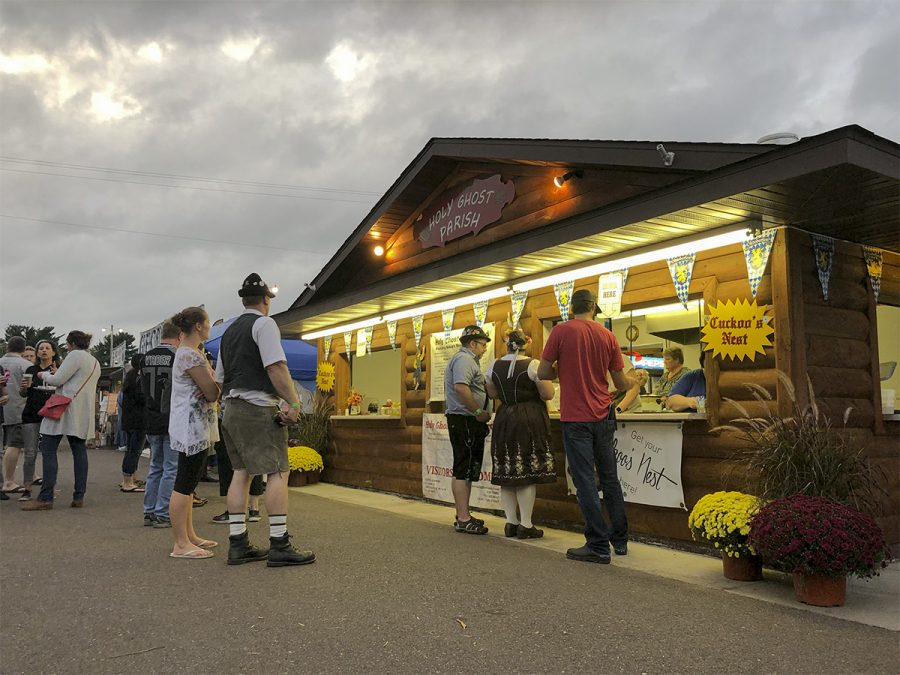 Oktoberfest visitors waited in line to purchase food from the Holy Ghost Parish. Some participants dressed in traditional German Lederhosen and Dirndl.