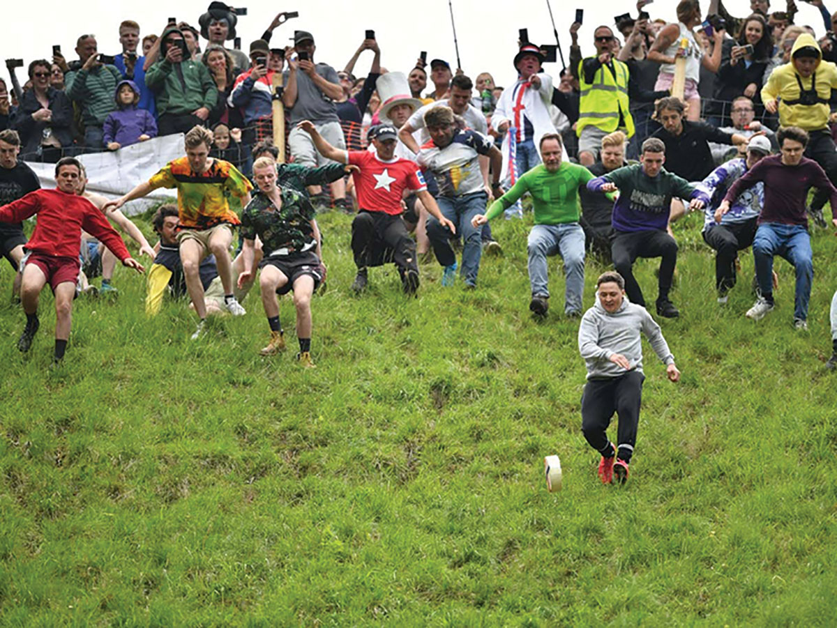 Cheese-racers tumbled down Cooper's Hill in the first men's downhill race, with eventual winner Max McDougall out front, the Independent said.