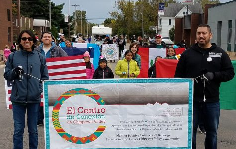 Gerardo Licón walks in a parade with other members of El Centro de Conexión de Chippewa Valley during the International Fall Festival in 2018.
