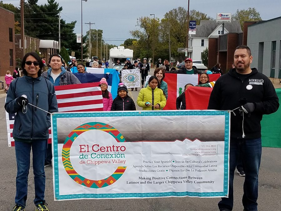Gerardo Licón walks in a parade with other members of El Centro de Conexión de Chippewa Valley during the International Fall Festival in 2018.