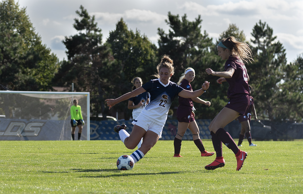 Midfielder Anna Kautzman kicks the ball as Augsburg forward/midfielder Jennifer Bobaric blocks.