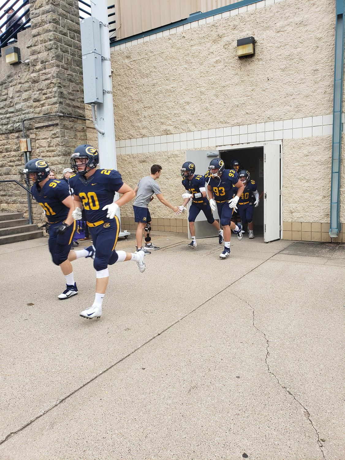 The Blugolds run out to face the Loras Duhawks
