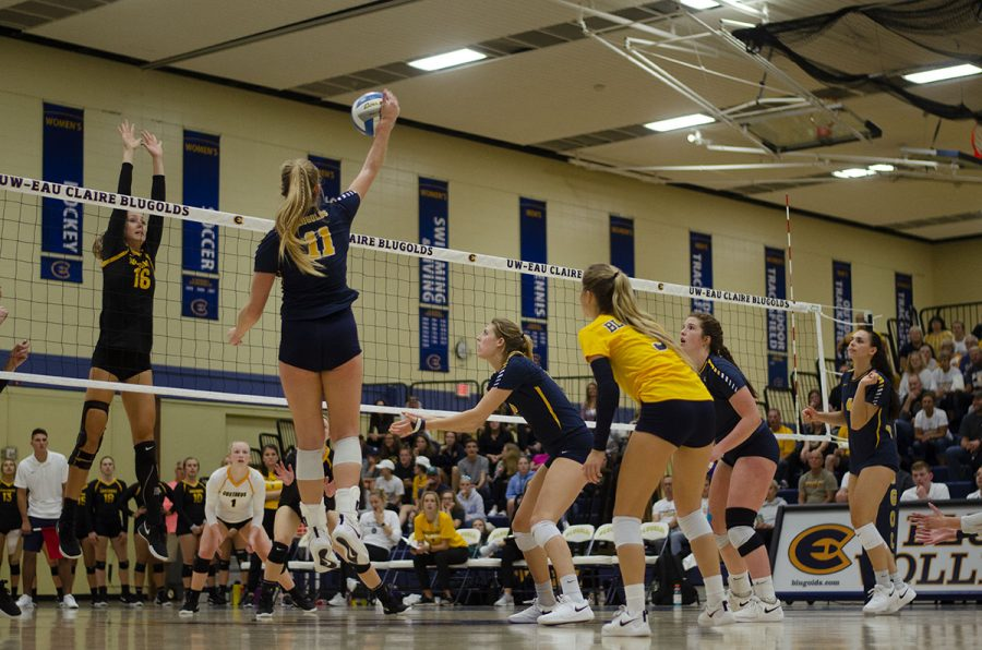 Mackenzie+Bachmann+jumps+up+to+spike+down+the+ball+as+Gemma+Robey+of+Gustavus+Adolphus+prepares+to+block+the+hit.+Meanwhile%2C+the+Blugolds+on+the+court+gather+to+pick+up+the+block.