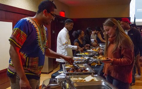 Shawn Smith, a first-year student, served food to attendees at the African Dinner event.