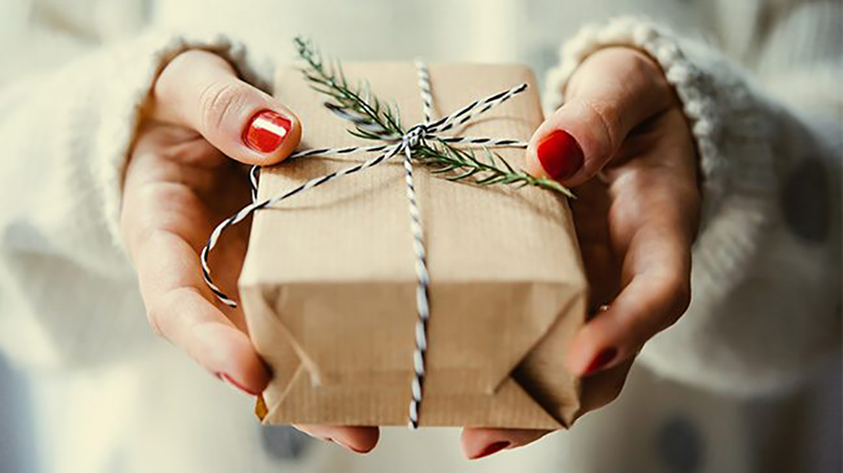 Pictured is a small gift being handed to a loved one.