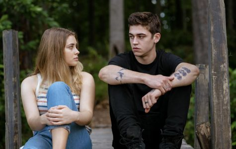 A teen boy and girl sit on a dock.