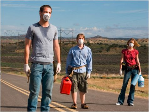 Three people with face masks stand in a road.