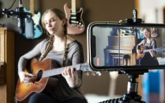 A smartphone recording a woman playing guitar.