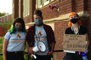 """Event organizers Stephanie Hoeksema, Jacksen Wolff and Maja Samec stand outside of Schofield Hall after the """"Cops off Campus: Dare to Divest"""" rally. The group posted messages onto Chancellor James C. Schmidt's office."""