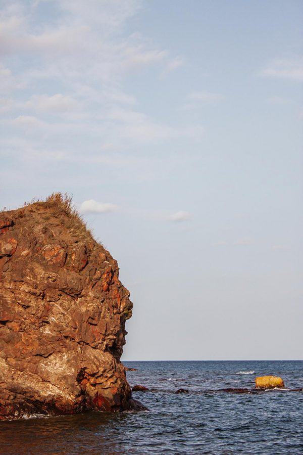A cliff stretches out of the deep waters of Lake Superior.