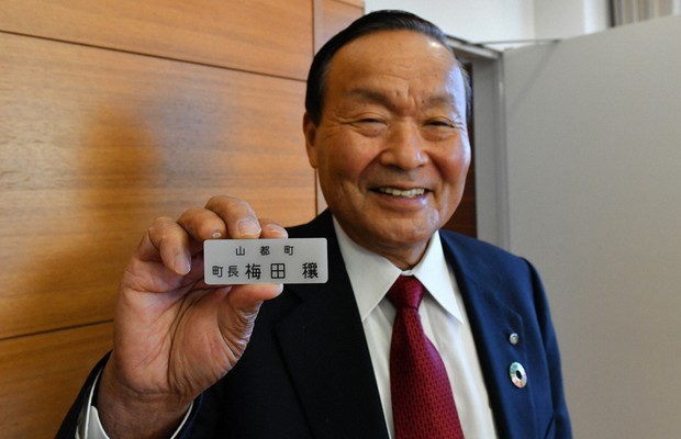 Mayor Yutaka Umeda smiles while holding his name plate at town hall (Mainichi/Kohei Shimizu)