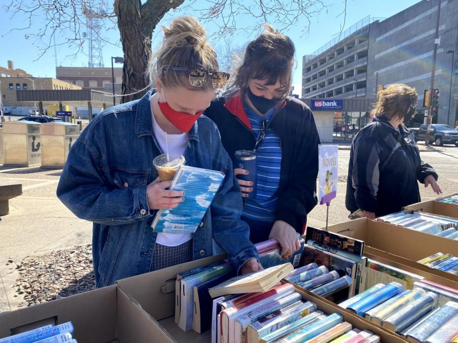 Students and community members gather at the L.E. Phillips Memorial Public Library to buy books on a warm spring day.