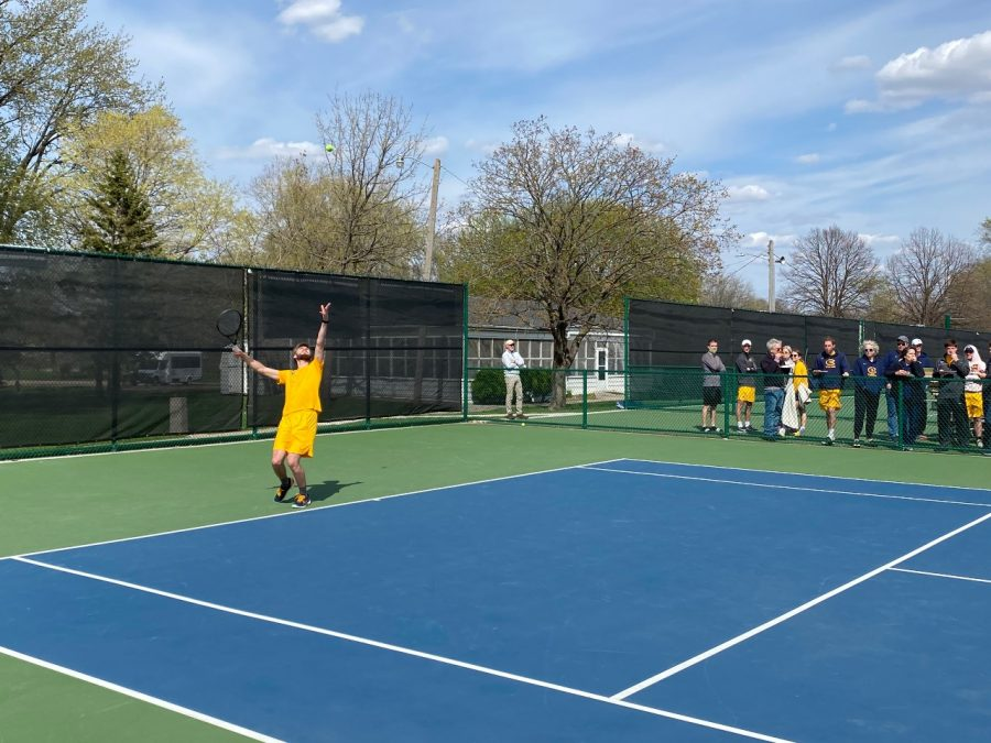 Grant Mauthe serves during one of his last college matches as his father and the rest of the Blugolds men's tennis team cheer him on.
