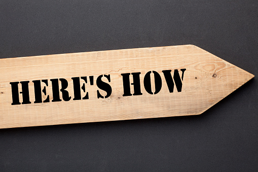 Heres how text on directional wooden arrow. How to
